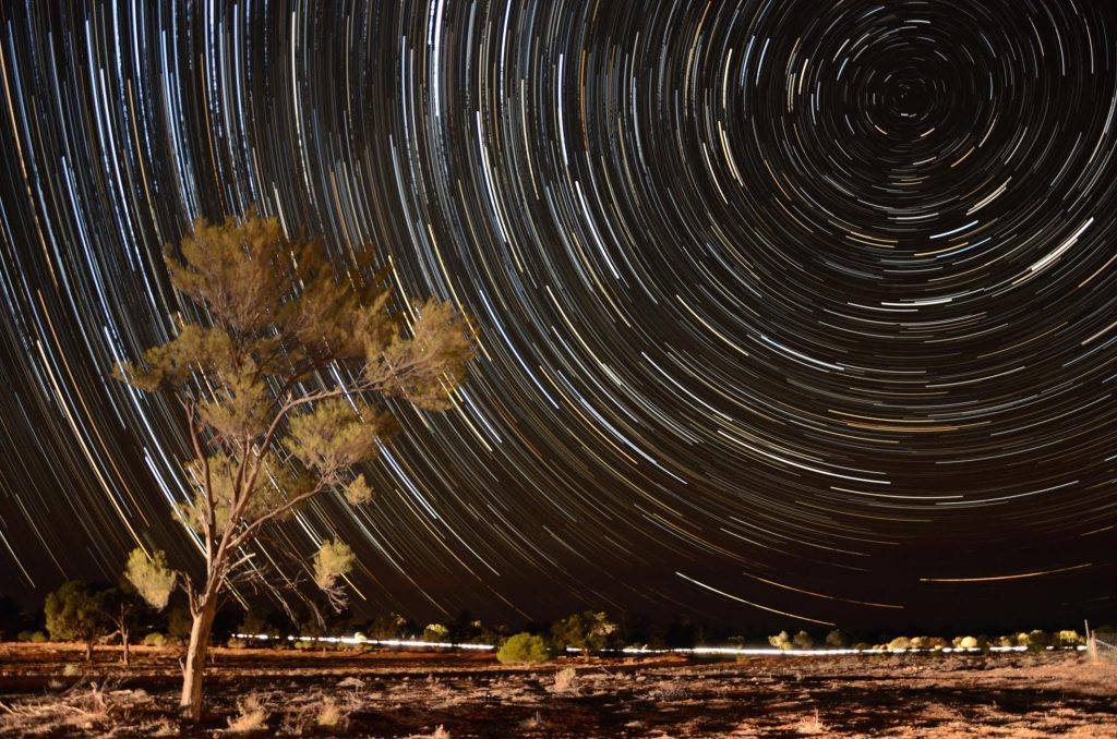 The rotation of the Earth beneath the night sky produces star trails in this 75 minute time exposure, while passing car headlights illuminate the foreground, Nanya Station, NSW, Australia