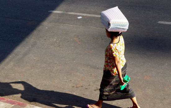 woman on street carrying bag on head 550x350